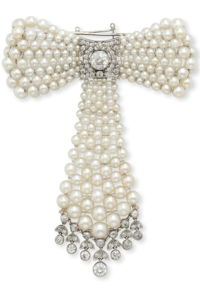 A BELLE ÉPOQUE PEARL AND DIAMOND BOW BROOCH. Designed as a pearl ribbon bow, set at the centre with a bezel-set old European-cut diamond, within a single-cut diamond plaque, suspending a detachable pearl tassel, trimmed with an old European and single-cut diamond fringe, mounted in platinum, circa 1910.