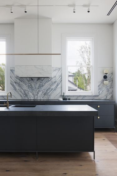 Blue and white modern kitchen with marble back splash 2/3 up the