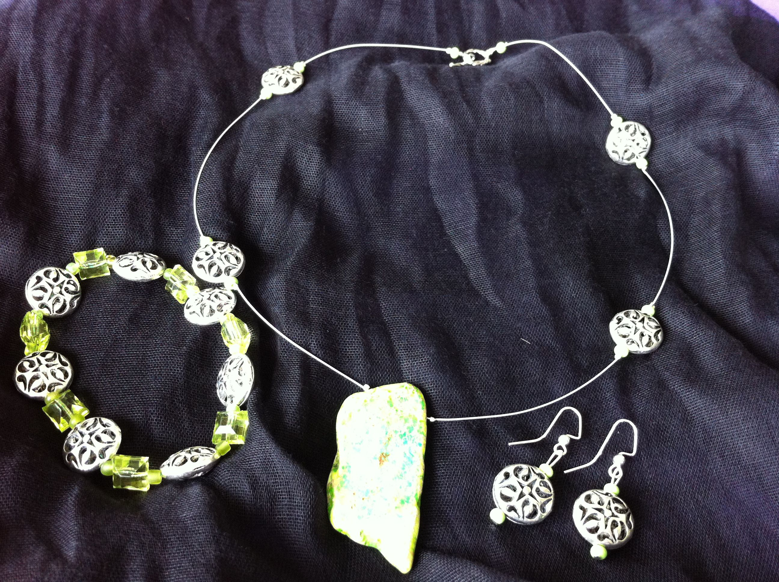 3 pc set includes necklace with green stone and antiqued silver beads, bracelet has antiqued silver beads and green beads, and earrings have antiqued silver and green seed beads with silver earwigs