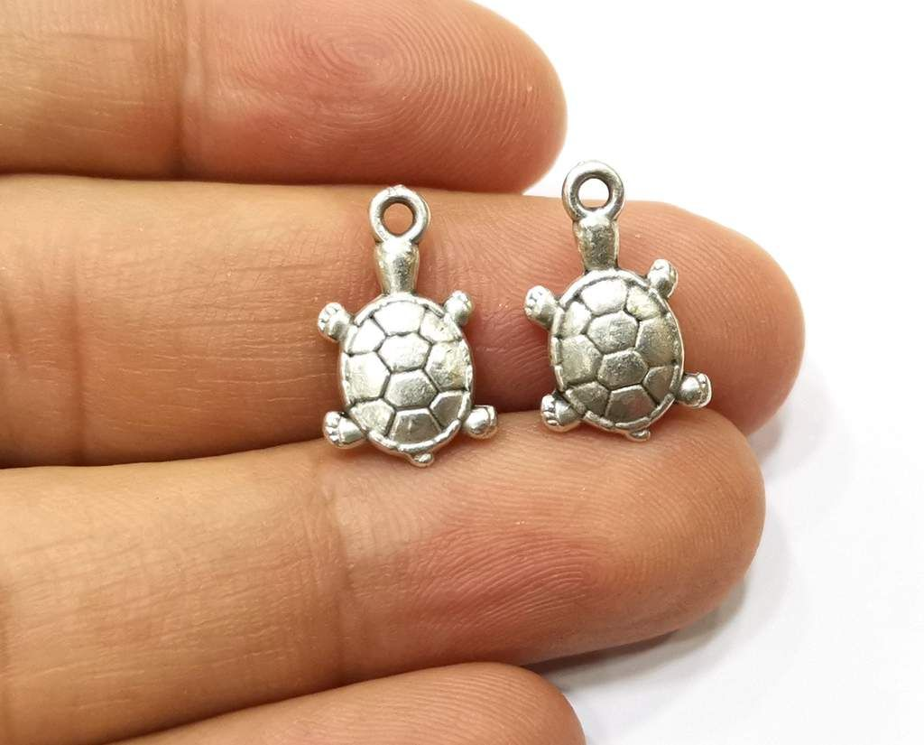 10 Sea Turtle Charms Antique Silver Plated Charms (18x11mm) G18128 Material : Zinc alloy, Nickel free and Lead free metal Color: Antique Silver Size : 18x11 mm Quantity : 10 pcs.