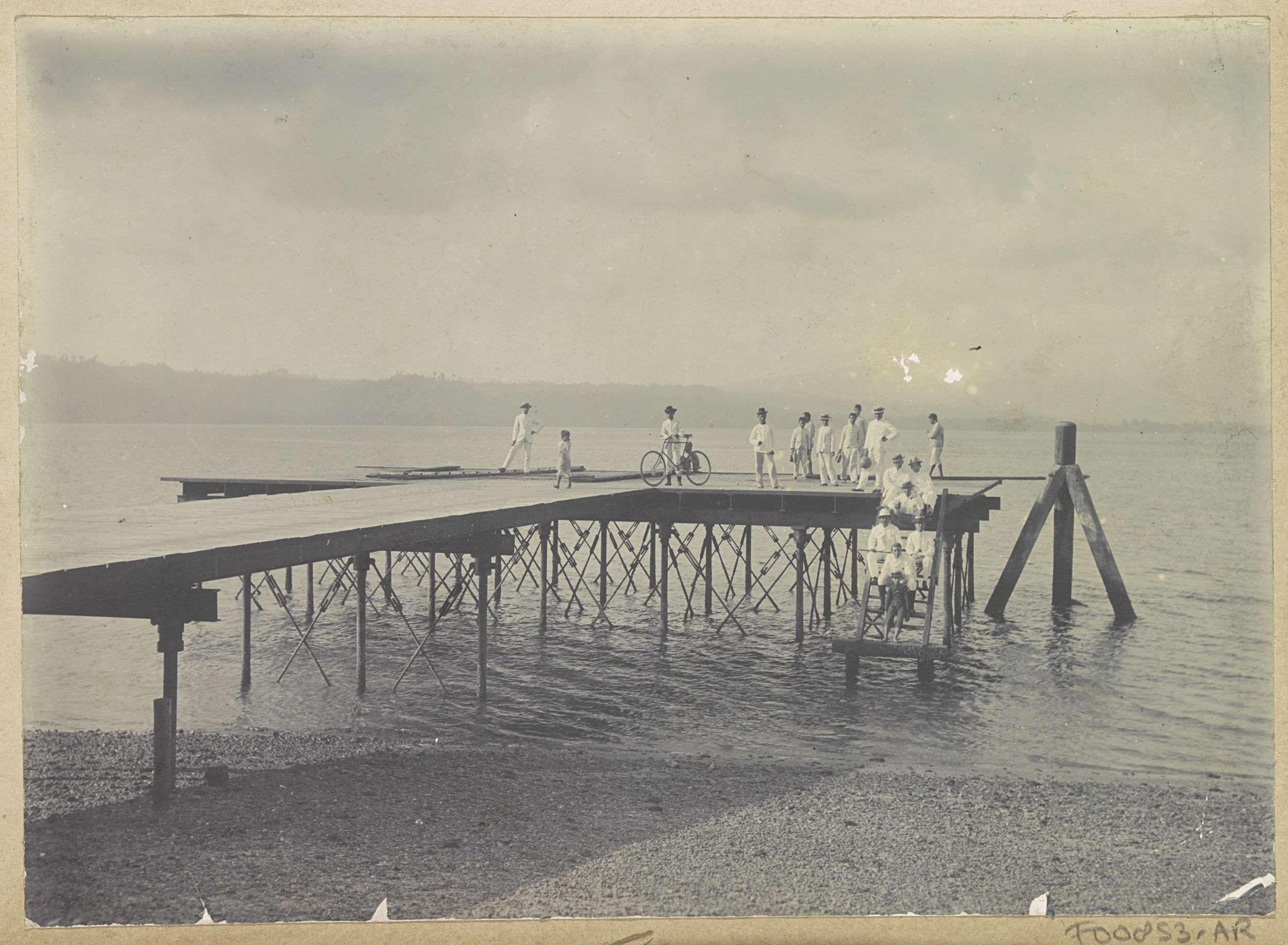 Anonymous | Plankier aan een water met mannen op Ambon, Anonymous, c. 1900 - c. 1920 | Onderdeel van Reisalbum met foto's van Ambon.