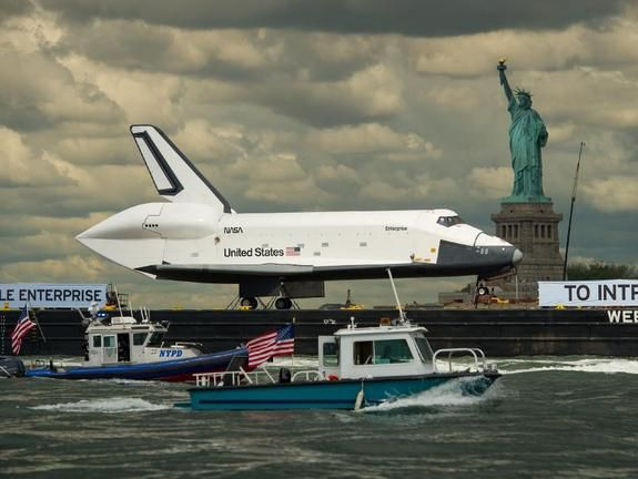 Shuttle in Hudson- Bet Lady Liberty never thought she'd see something like this. The Space Shuttle Enterprise was towed past the Statue of Liberty Wednesday (June 6, 2012) through the Hudson River on its way to to the Intrepid Sea, Air and Space Museum, where it will go on permanent public display.