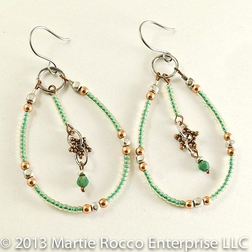 These large hoop earrings are designed with seed beads which are clear glass with a green lining so the effect is light and three dimensional. I've accented with copper and silver brass beads. The i