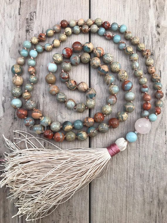 Soft tones of blue, brown, and beige make up the beautiful tones in this African Opal jasper mala necklace. Faceted Rose Quartz Guru bead is followed by a silver accent and amazonite bead. Beautiful ecru silk tassel with rose banding finished this calming piece. The jasper stones in this mala #africanbeauty
