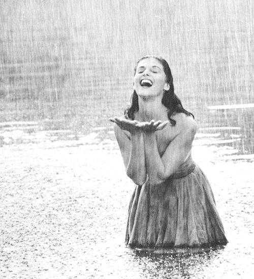 Pier Angeli, 22, clad in strapless chiffon party dress, exhulting in a downpour of rain as she stands knee deep in a woodland pond, photographed by Allan Grant for LIFE Magazine, 1954.