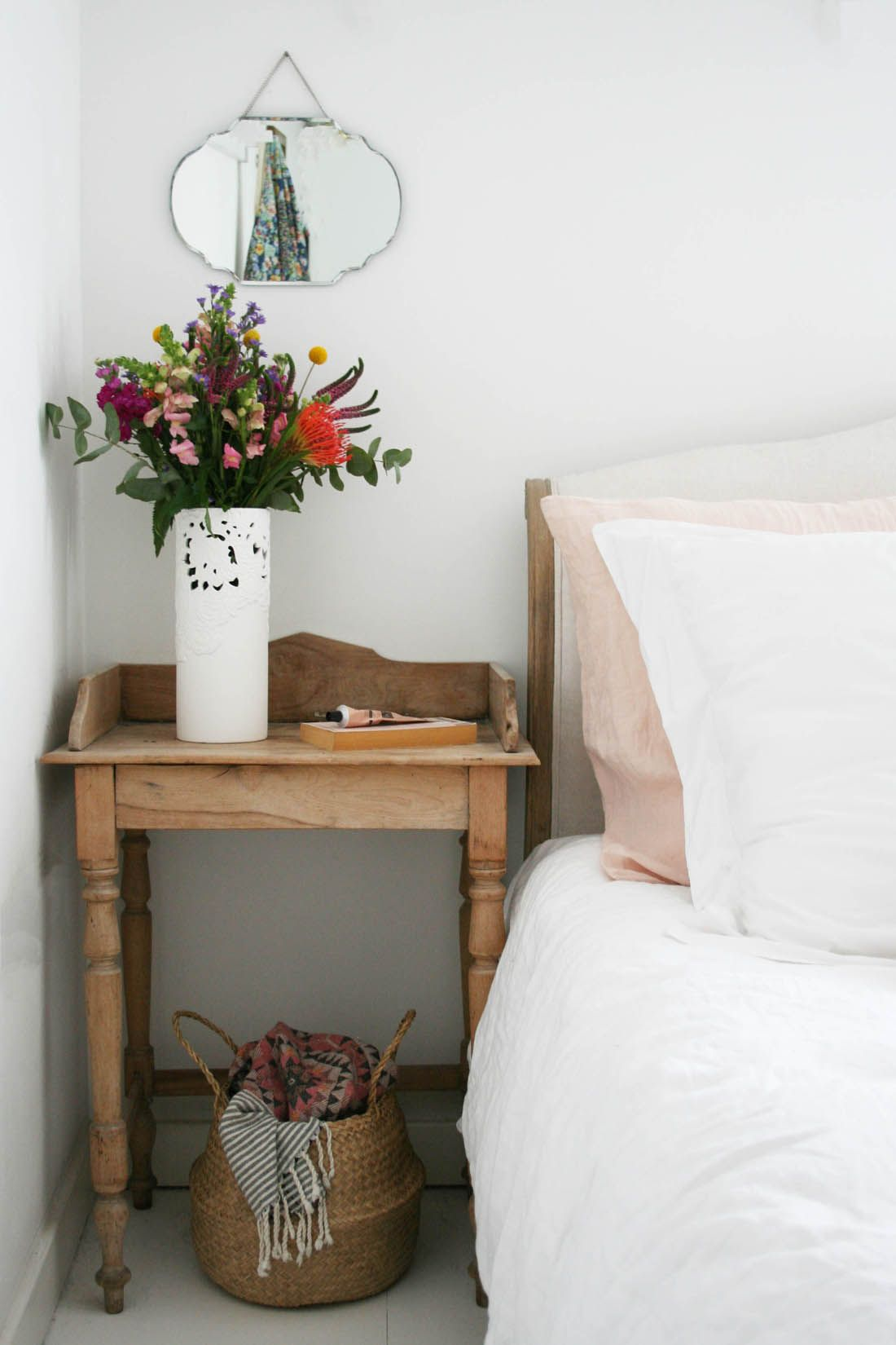 minimal white bedroom with accents of dusky pink and vintage bedside table with an autumnal bouquet of flowers