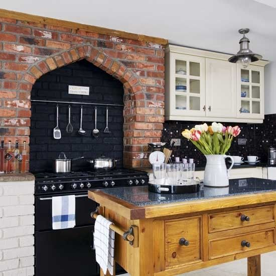 An Exposed Brick Feature Wall Showcases A Dramatic Range Cooker The Black Splashback And Worktops