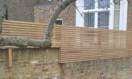 Top Of Wall Iroko Panels Brick Wall Gardens Garden Fence Panels Trellis Fence Panels
