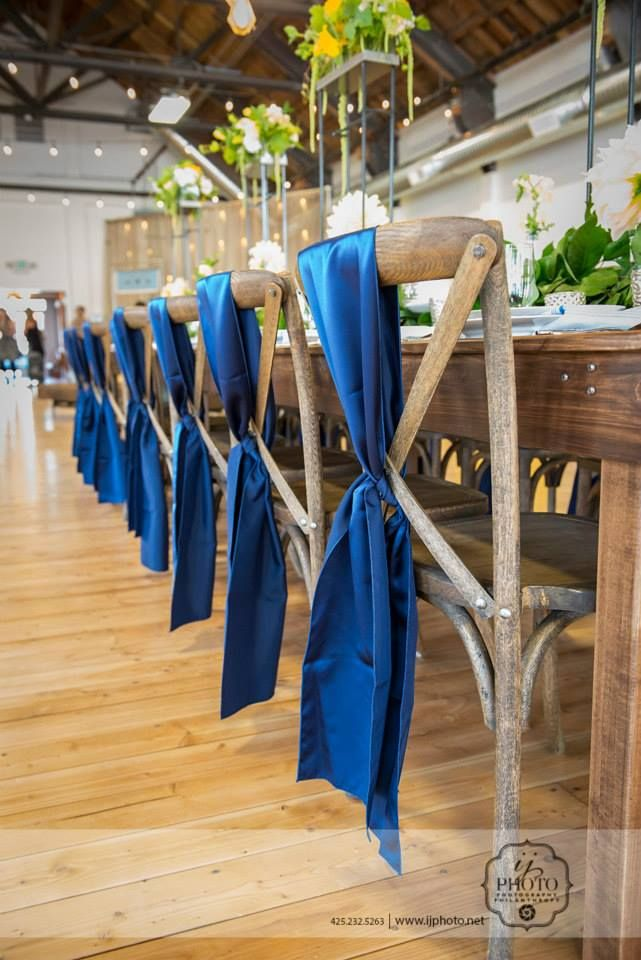 Our rustic Vineyard Chairs tied beautifully with navy sashes, around our new Farm Table