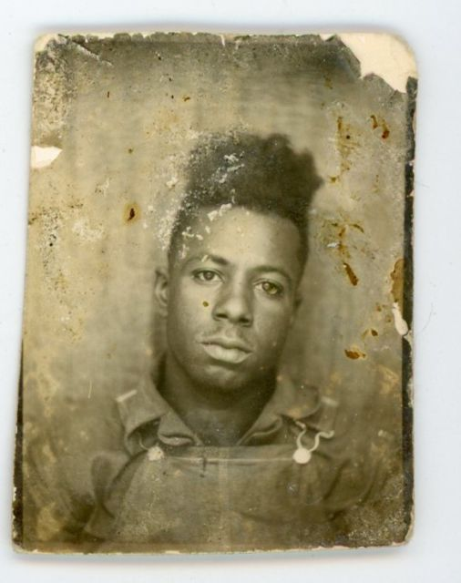 African American man in denim overalls. Melancholy vintage photo booth photo (dig the high-top!)