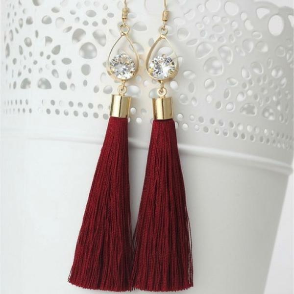 "Burgundy Tassel Earrings with Gold Oval and Crystal Burgundy tassels dangle from a gold oval with a shimmering crystal. Boho style earrings. Earrings measure 2 1/2""."