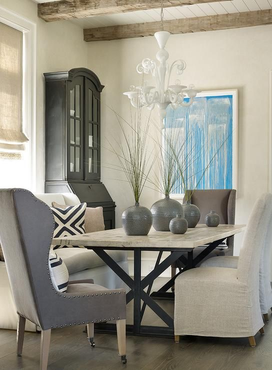 Lovely dining room features an iron x based dining table lined with
