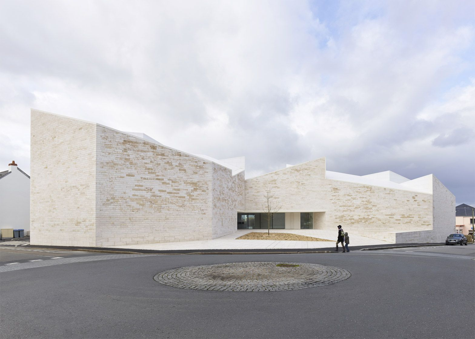 Atelier Fernandez & Serres has completed a cultural centre featuring travertine walls and sloping roof planes that echo the forms of neighbouring houses