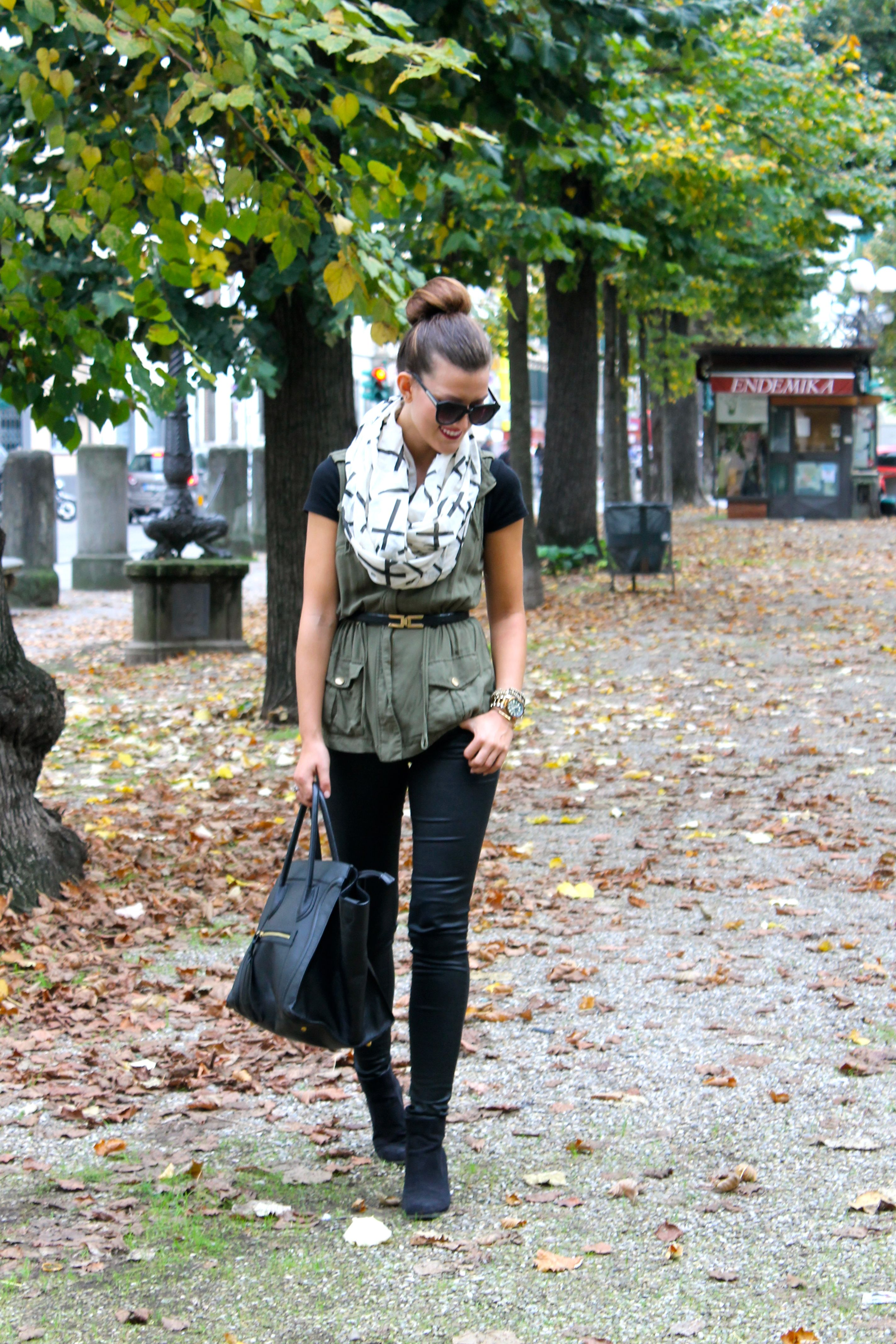 Military vest, black jeans, black tee black sunnies and black and white print scarf