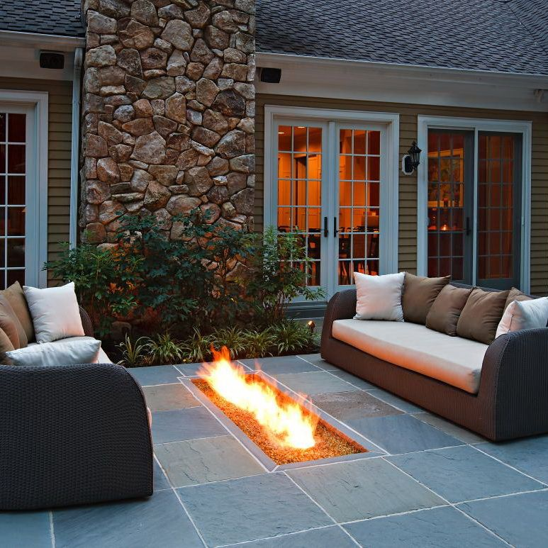 An in-ground fire pit lights and warms up this patio sitting area. A pair of wicker sofas flank ...
