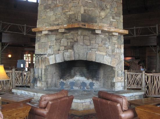 stack stone fireplace in large sitting area has beautiful views .