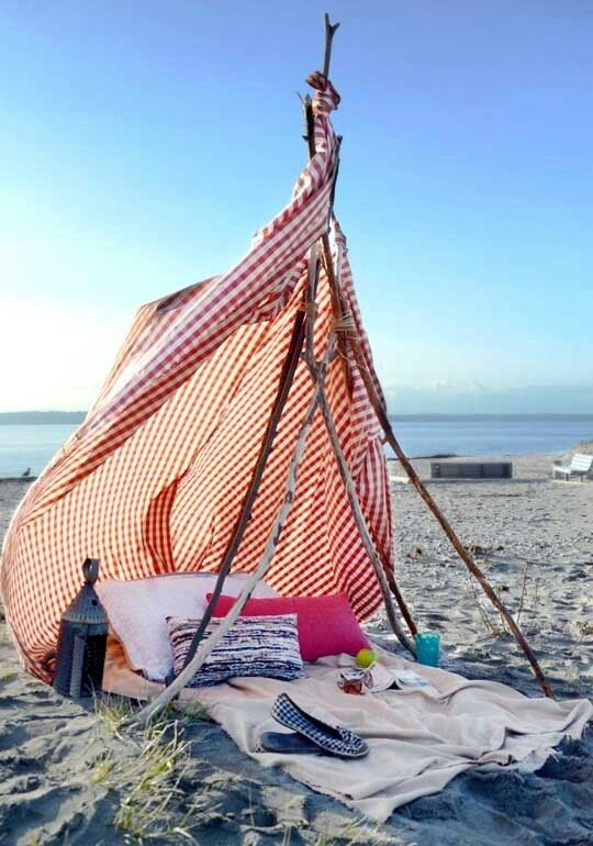 Too lazy to carry around massive beach umbrellas? Create a make shift teepee out of a picnic blanket and some branches
