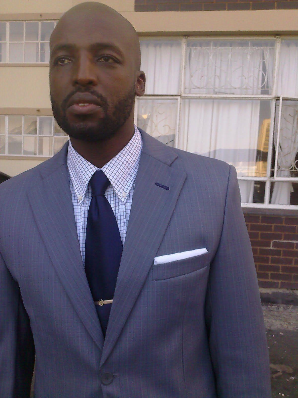 Grey suit, light blue shirt, navy tie.