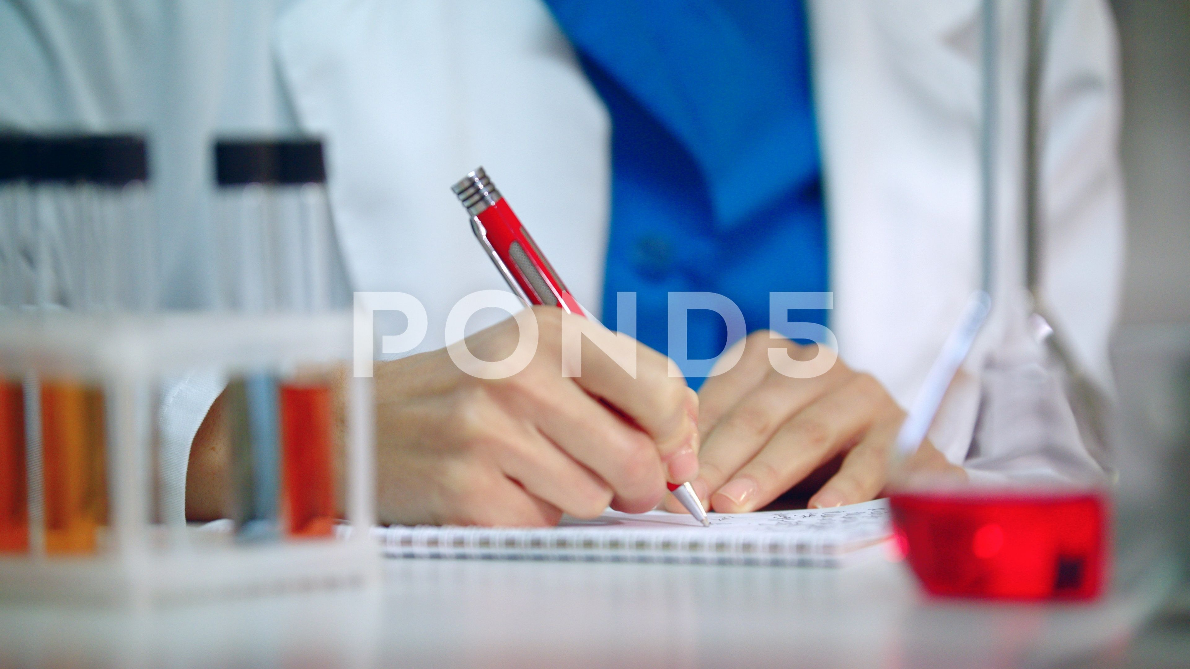 Lab researcher writing research report. Medical student