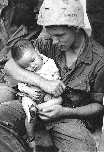 American Marine comforts orphaned Vietnamese child, 1969