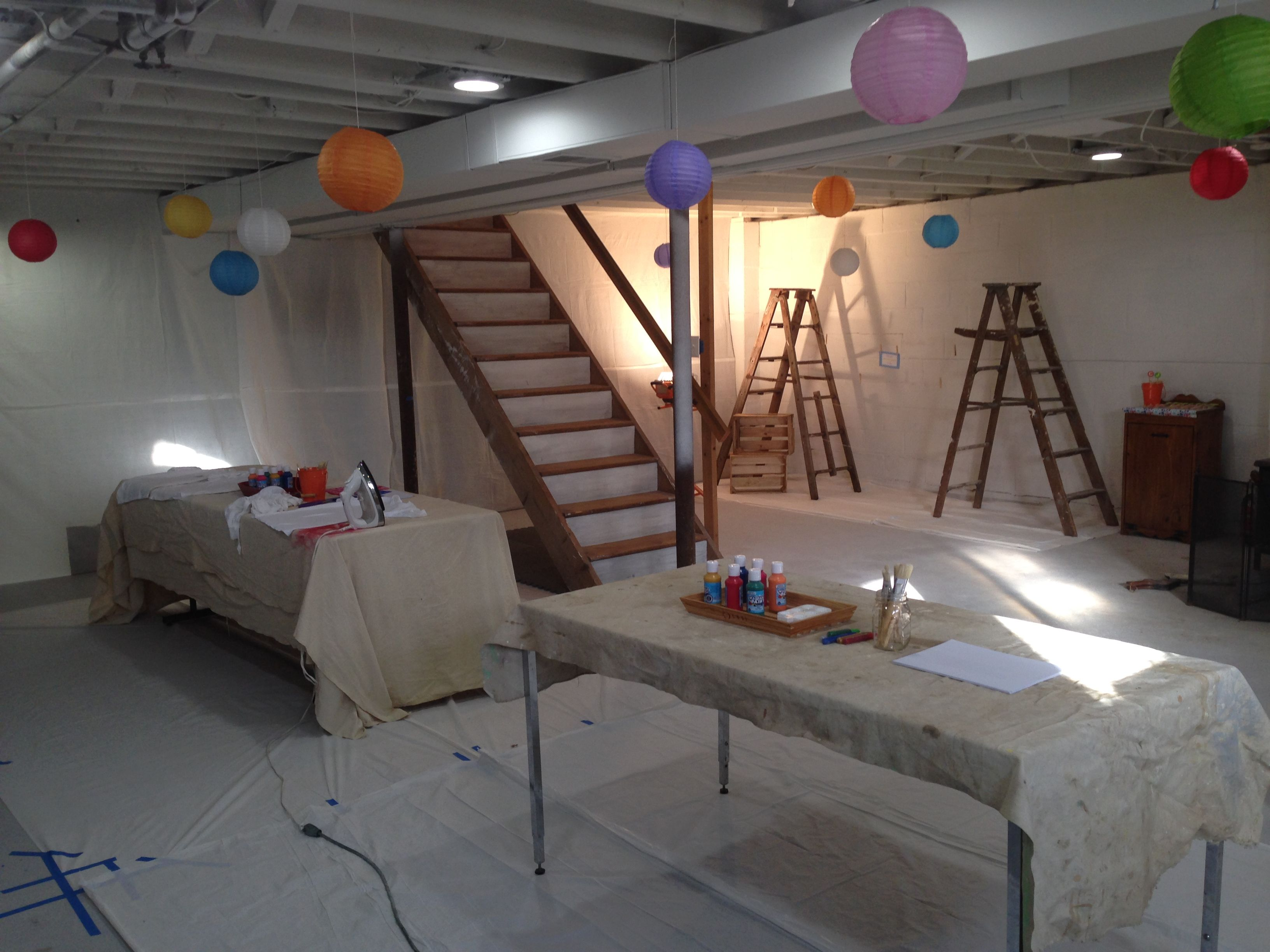 painting party set up in the basement.  drop clothes as table clothes.  paper drop clothes taped to the floor.  and paper lanterns hanging as more rainbow polka dots.