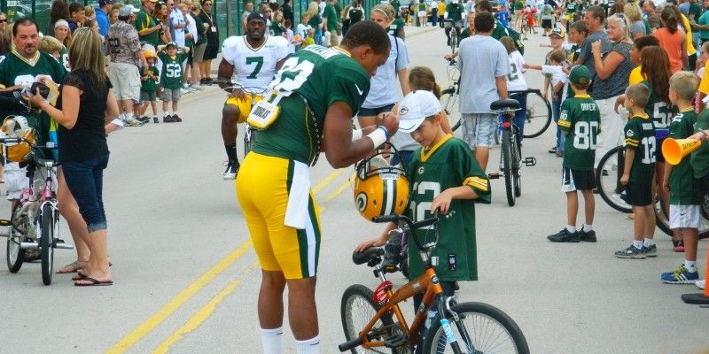 Green Bay Packers Training Camp Tradition | Kids line up for the opportunity to have their favorite player ride their bike and sign an autograph.