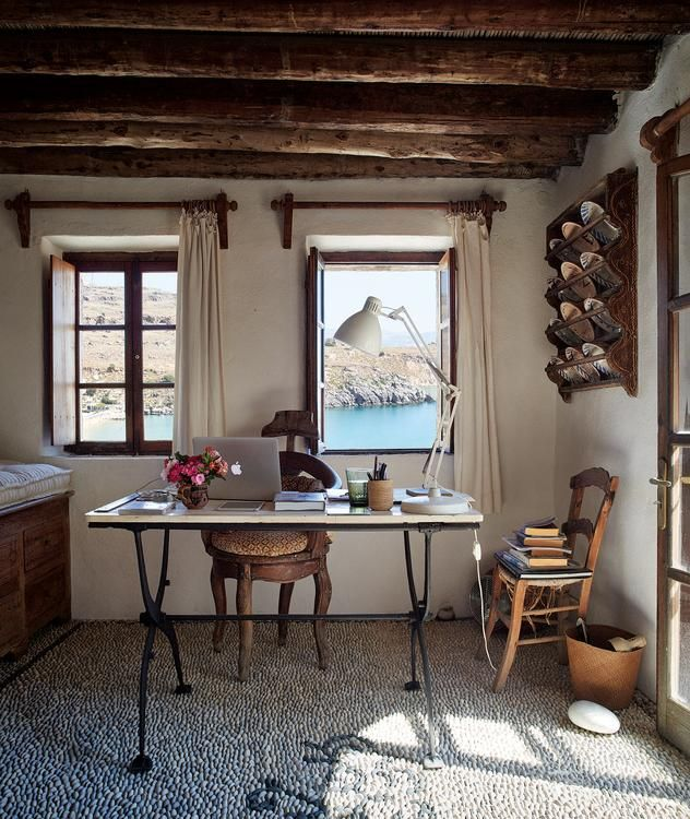 WINDOWS ON THE WORLD | Conran's office boasts an antique stone table, a barber's chair and a vintage task lamp. The view is of Lindos harbor.