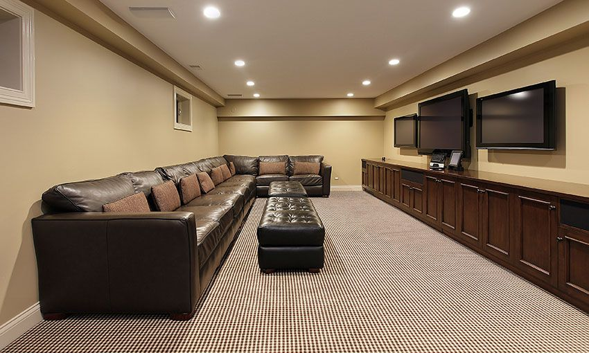 Basement Living Room With Multiple Tvs And Long Brown Leather Couch Ottoman