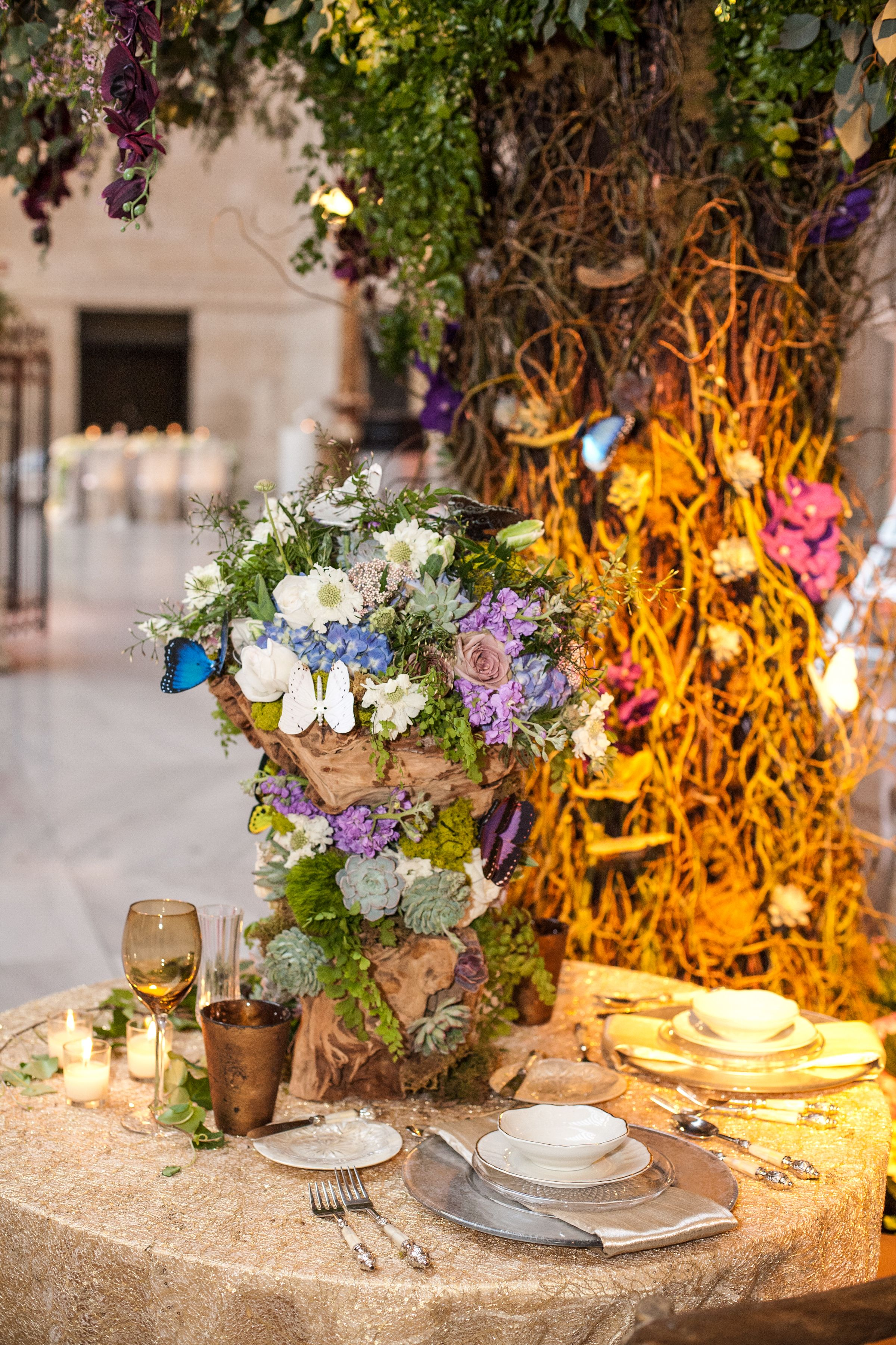 A whimsical centerpiece with animated butterflies on a beautiful gold sequin chain overlay provided by Nuage Linens. Photo by: @Carasco Photography