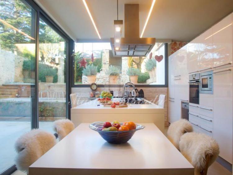 Vista de la mesa del comedor y la cocina con la vista del jardín
