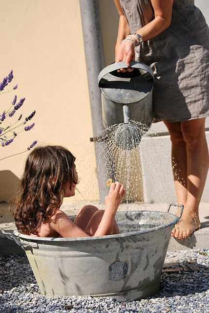 Watering-can bath, mother and daughter.