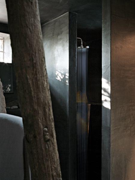 La malta cementizia sui toni del grigio rende riconoscibili i nuovi interventi: il guardaroba e il bagno dal grande lavabo in pietra scavata.