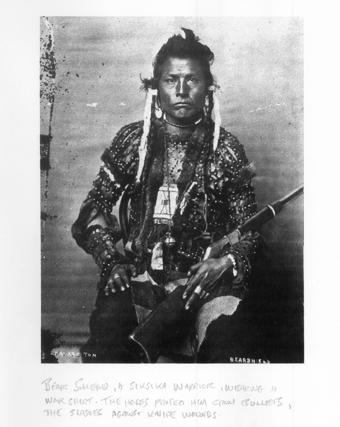 Bearshield, Siksika [Blackfoot Canada] warrior, with his war shirt, the hold protected him from bullets and the slashing protected him from knife wounds.