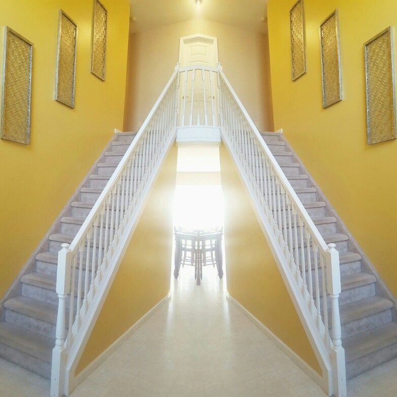 Here\'s a view of my bare stairway, yellow wall, some wall decoration ...