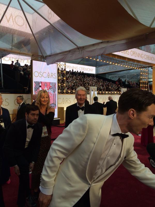 #BenedictCumberbatch on the #Oscar red carpet. The gentleman behind him is dad #TimothyCarlton preparing to #photobomb