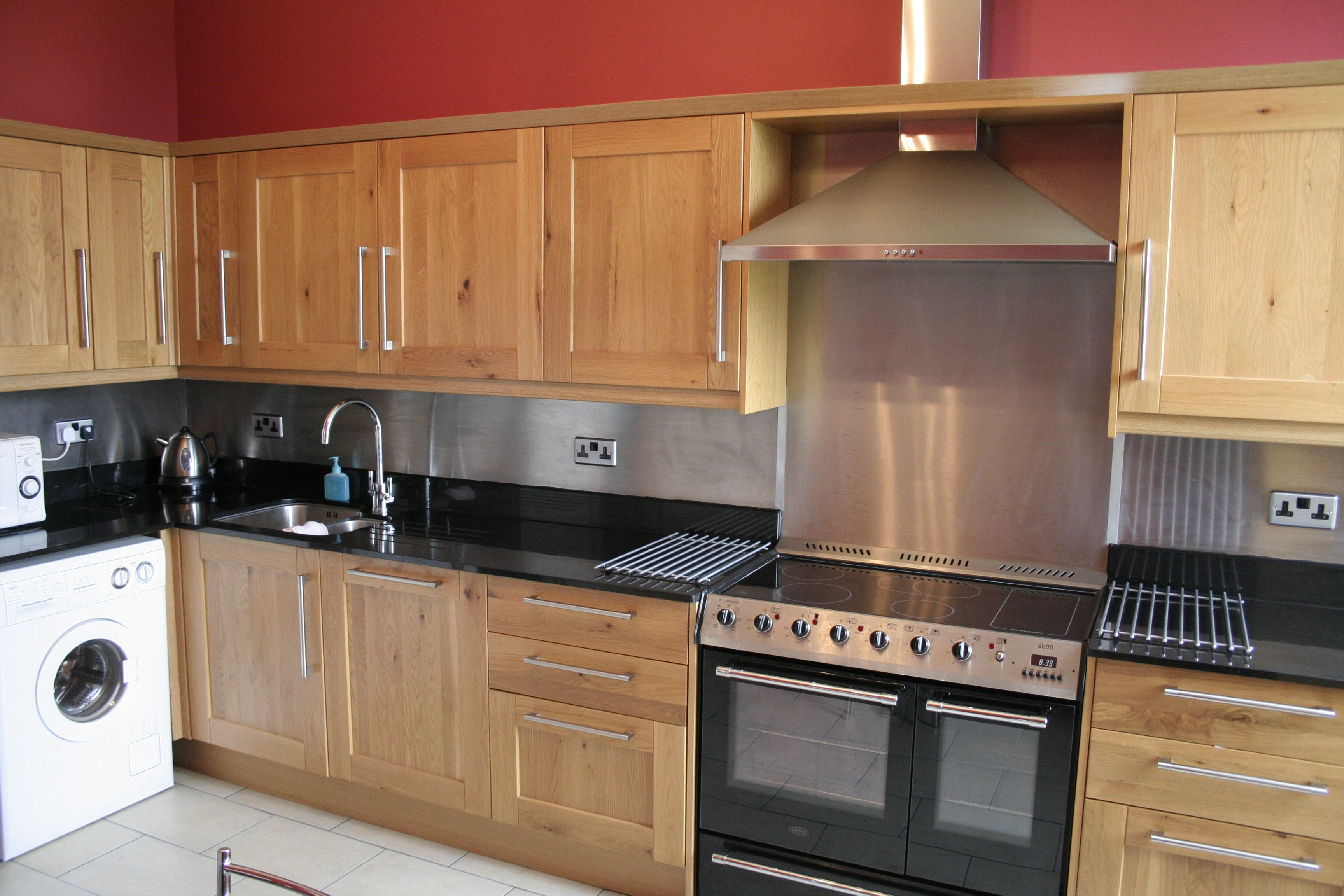 Red Kitchen With Stainless Steel Backsplash And Appliances