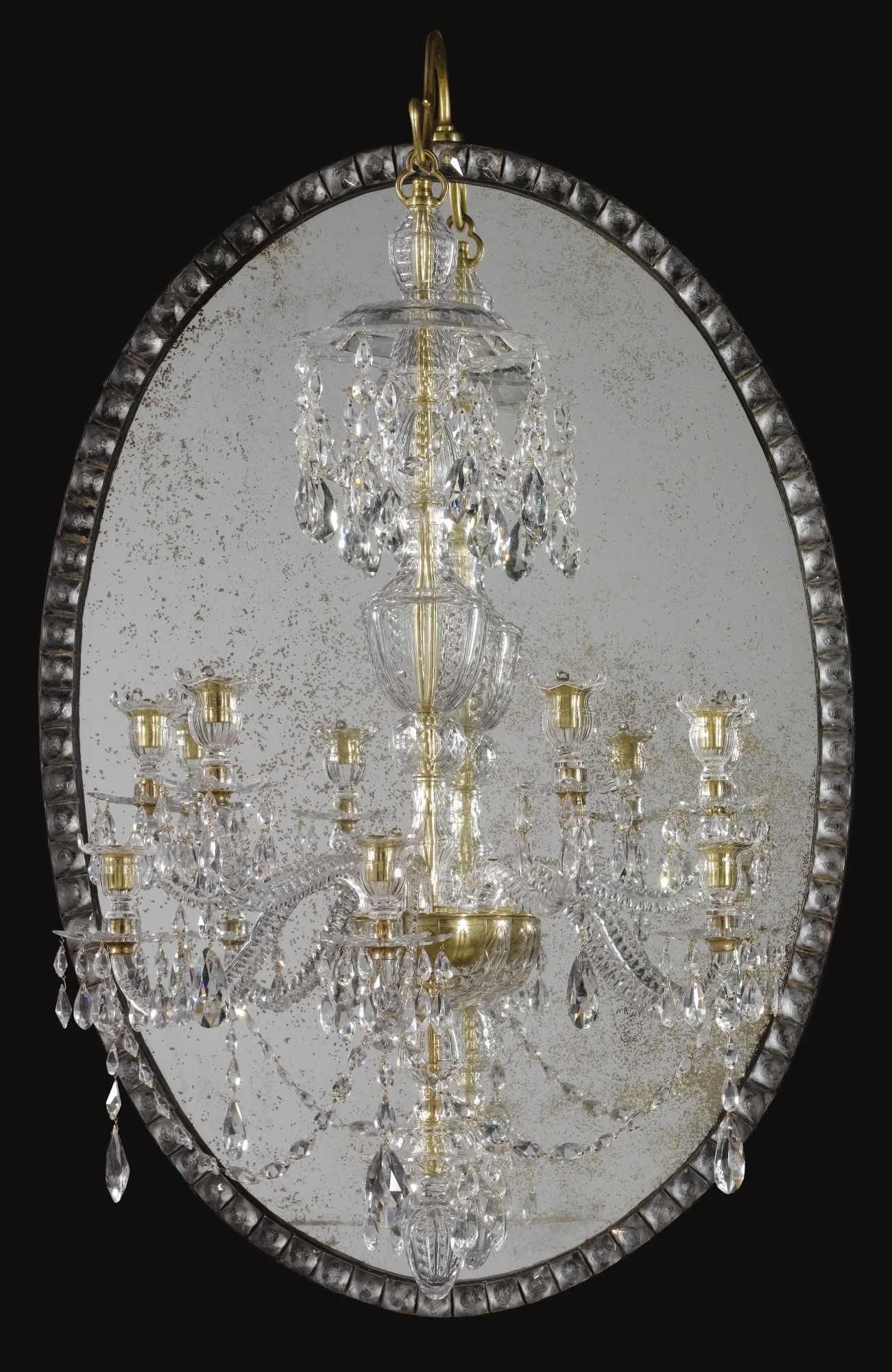 A George III cut-glass mirror chandelier Irish circa 1790 the oval mirror with a border of faceted drops, the chandelier with seven lights with a slender baluster stem surmounted by a canopy hung with drops above the candle arms, similarly hung, with a pendant finial below.