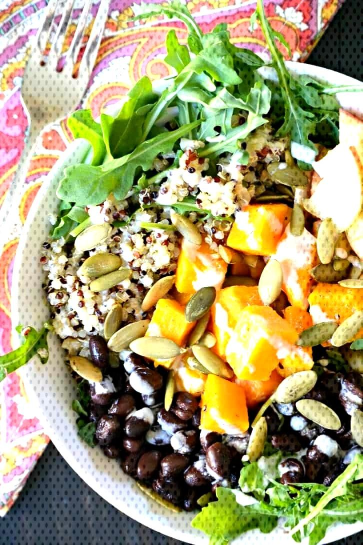 Butternut Squash Vegan Buddha Bowl combines arugula, quinoa, black beans, apple, pumpkin seeds, and