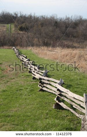 Stock Photo A Split Rail Fence Runs Down A Hill Next To A Field
