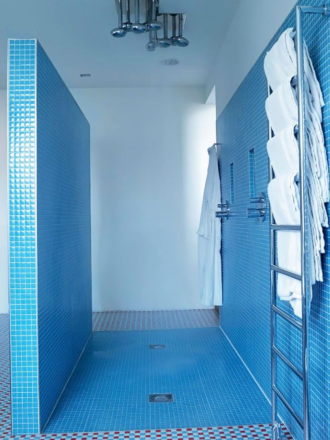 Blue mosaic tile walk-in shower with towel warmer and robe hooks close at hand