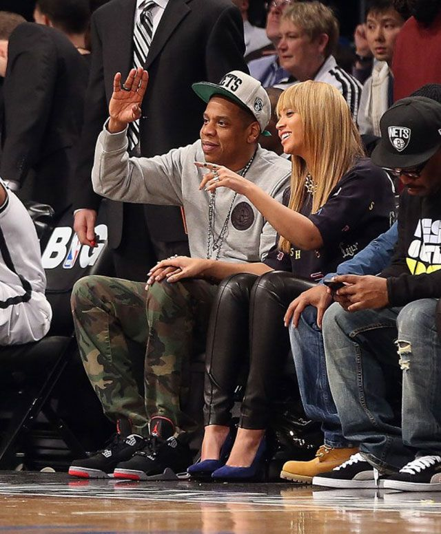 Jay-Z wearing Air Jordan IV Bred and mitchell and ness nets snapback at a