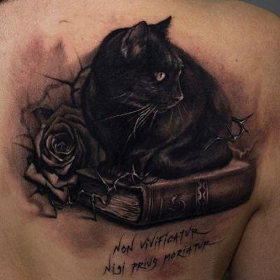 Black cat sitting on a book tattoo