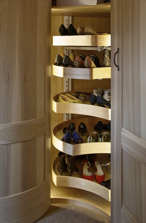A shoe carousel in a corner unit in a walk in wardrobe