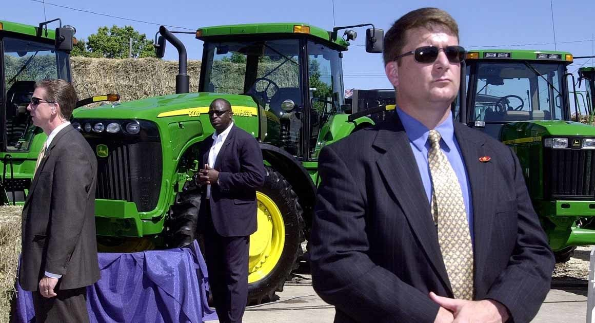Secret Service agents stand among tractors at the fair as