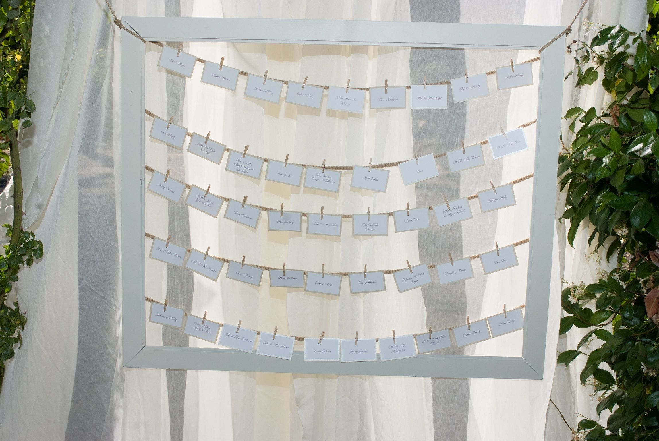 Seating chart: spray painted an old frame from good will and hung it in an arch with sheer material draped behind it!
