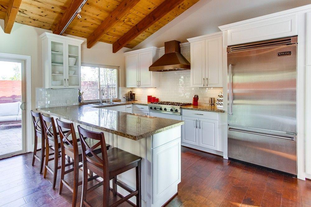 White kitchen cabinets glass tile backsplash viking appliances dark wood floors and granite countertops also