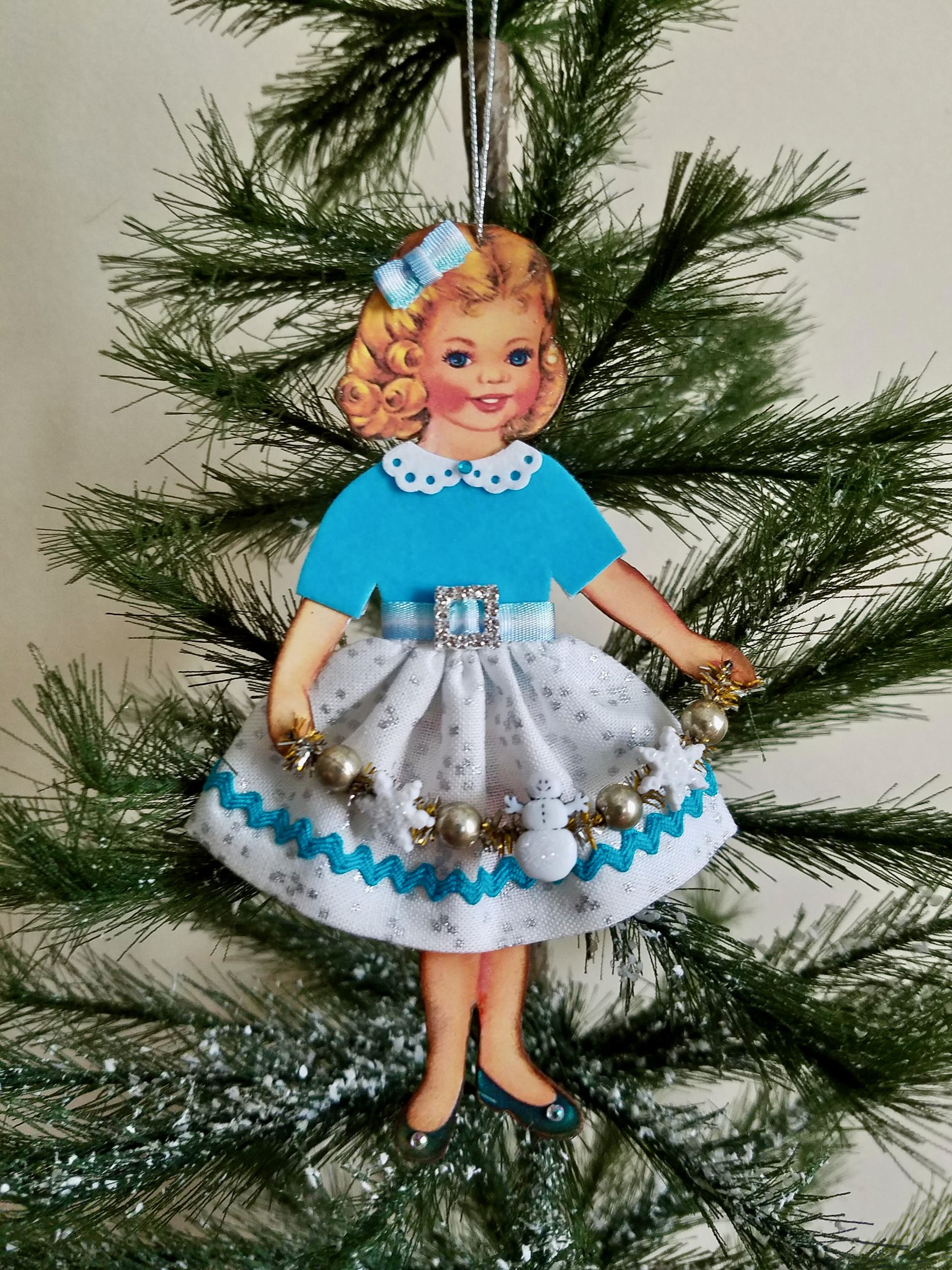 Handmade retro 50s paper doll ornament holding a tinsel