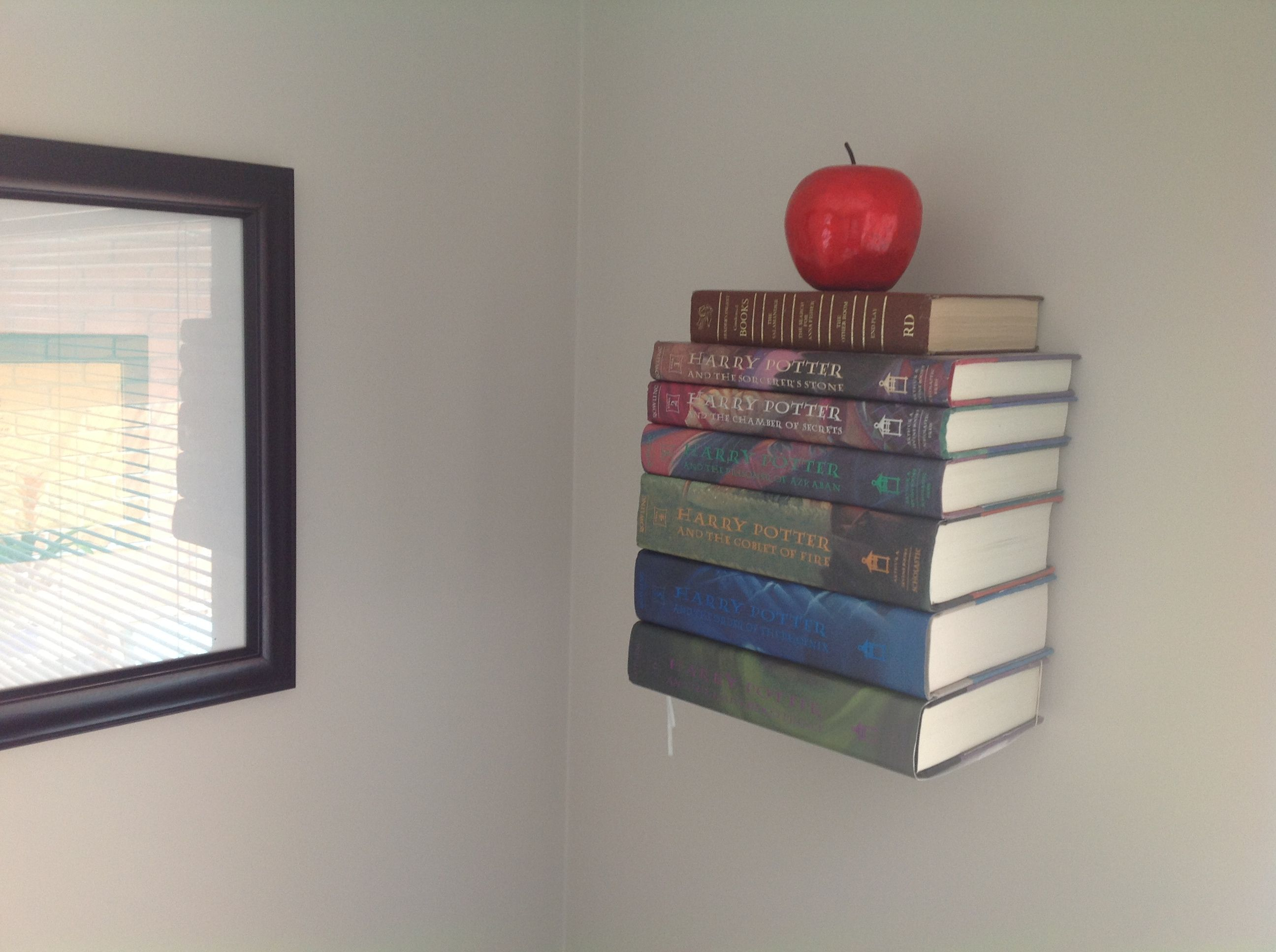 collection of harry potter books on bedroom wall