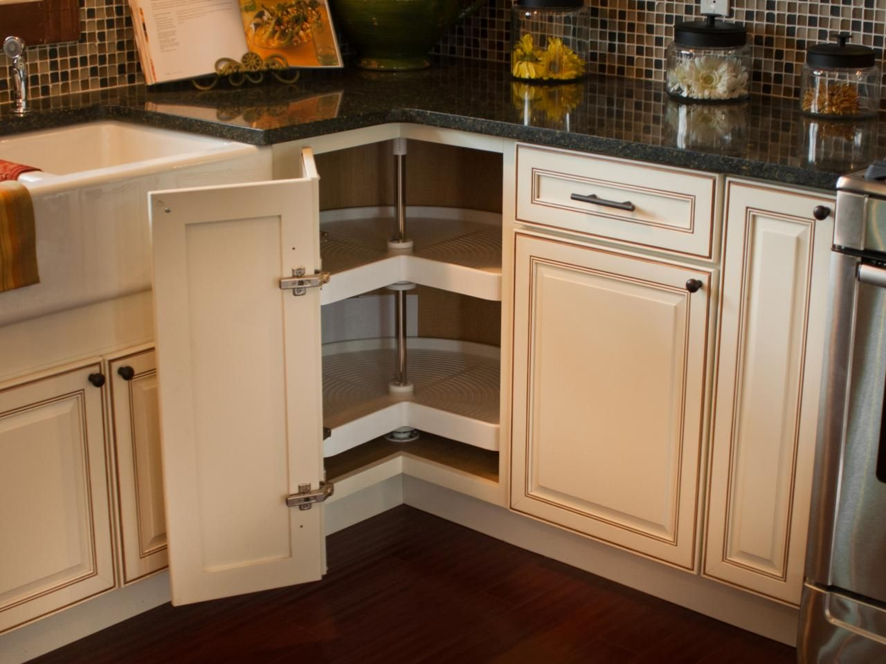 a corner cabinet door opens to reveal a kidney-shaped lazy susan