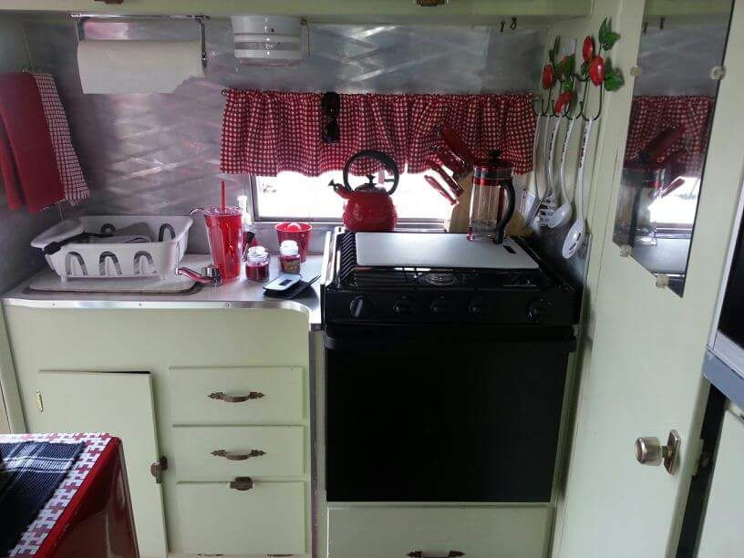 Kitchen is at the rear, near entrance,  and facilities are behind the door on the right.